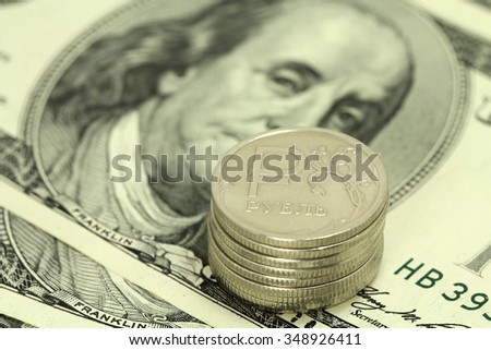 stack of coins of one Russian ruble against the background of one hundred dollars - stock photo