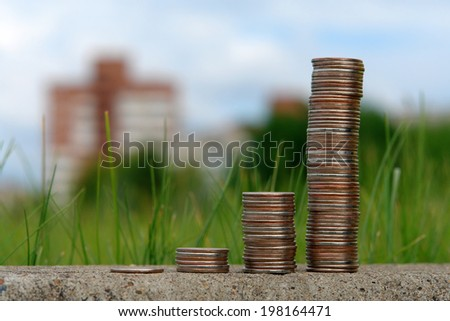 Stack of coins on a background of green grass and cities