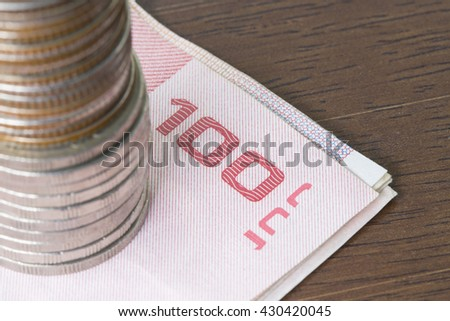 Stack of coins on bill on wooden table