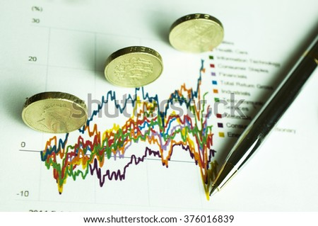 Stack of coins on financial graph paper analysis - stock photo