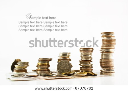 Stack of coins with bank notes isolated on white background - stock photo