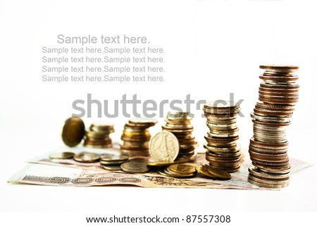 Stack of coins with bank notes isolated on white background. - stock photo