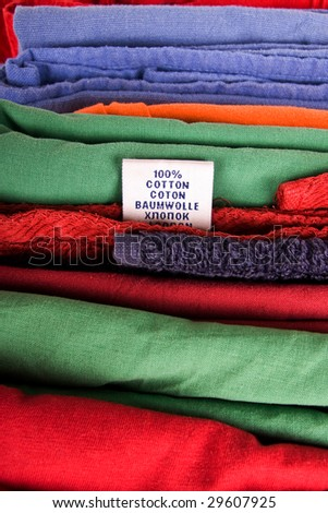 Stack of color textile clothes with label - stock photo
