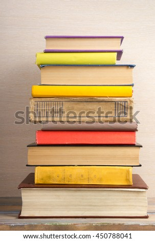Stack of colorful books, grungy beige background, free copy space Vintage old hardback books on wooden shelf on the deck table, no labels, blank spine. Back to school. Education background - stock photo