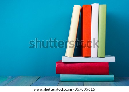 Stack of colorful books, grungy blue background, free copy space. Vintage old hardback books on wooden shelf, deck table, no labels, blank spine. Back to school,  education background. - stock photo