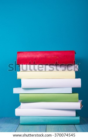 Stack of colorful books, grungy blue background, free copy space. Vintage old hardback books on wooden shelf, deck table, no labels, blank spine. Back to school,  instagram filter.  - stock photo