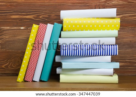 Stack of colorful books on wooden table. Back to school. Copy space for text