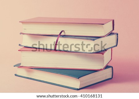 Stack of colorful books on wooden table. Education background. Back to school. Copy space for text. Toned image