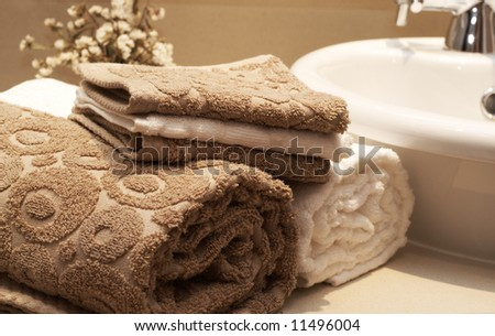 Stack of colorful brown and white towels on the table in the bathroom - stock photo