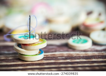 stack of colorful buttons with sewing needle on a wooden table. Focus on the needle's eye, very shallow depth of field - stock photo