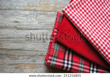 Stack of colorful dish towels on wooden table. - stock photo