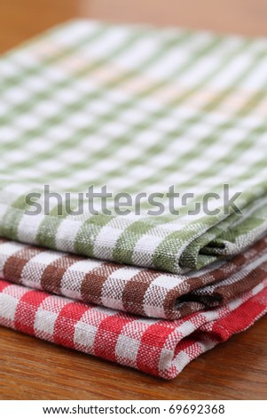 Stack of colorful dish towels on wooden table. Shallow dof - stock photo
