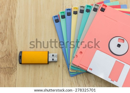 Stack of colorful floppy disks and a flash drive on a wooden table - stock photo