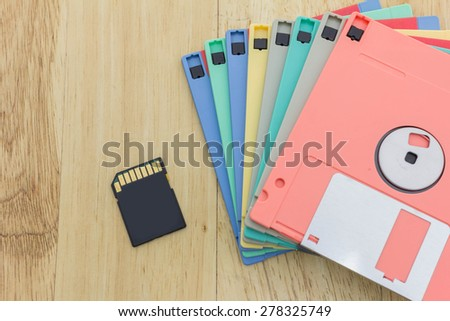 Stack of colorful floppy disks and a SD card on a wooden table - stock photo