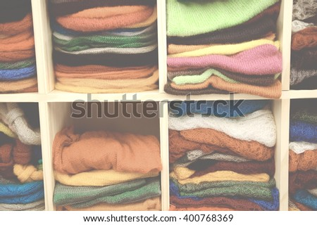 Stack of colorful  knitted colorful clothes - sweaters, dresses, cardigans etc. Toned photo with haze effect.  - stock photo