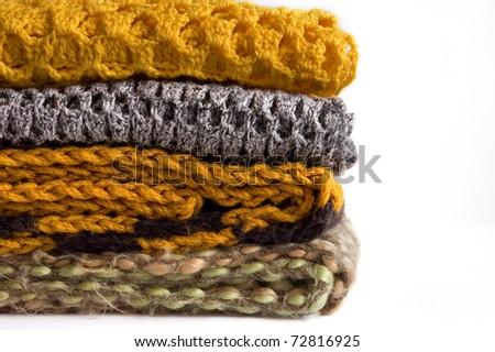 Stack of colorful knitted scarfs isolated on white - stock photo