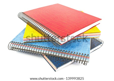 Stack of colorful spiral notebooks isolated on white - stock photo