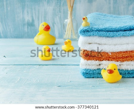 stack of colorful towels and bath duck on the table - stock photo
