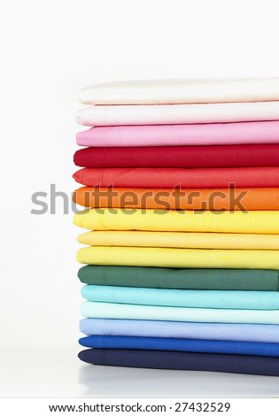 Stack of coloured linens on white background