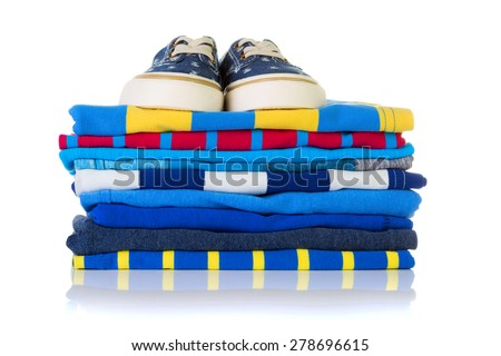 Stack of colourful summer shirts and a pair of sneakers on top isolated on white background - stock photo