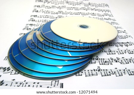 Stack of compact discs on a musical partiture