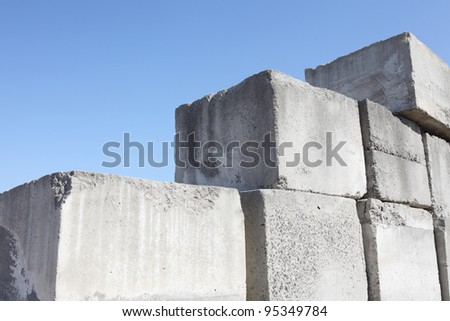 stack of concrete blocks, construction site against a blue sky - stock photo