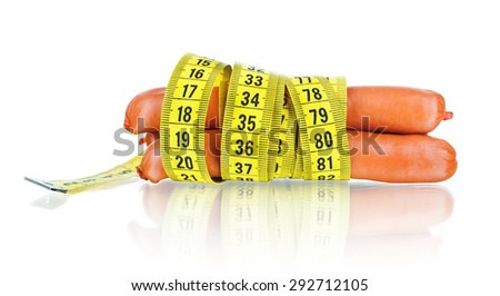 Stack of cooked sausages and measuring tape - stock photo