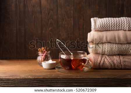 Stack of cozy knitted sweaters, big cup hot tea and cinnamon stick on rustic wooden background, selective focus. Winter Christmas Holiday time concept.