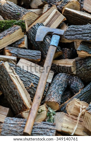 Stack of cut firewood logs for winter with an old axe - stock photo