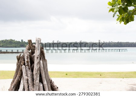 stack of cut logs fire wood by the sea and bridge background - stock photo