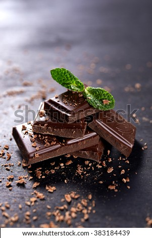 stack of dark chocolate and chocolate's crumbs. mint leaf on top of stack - stock photo
