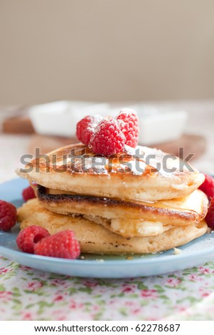 Stack of delicious and fresh american pancakes topped with raspberries and maple syrup - stock photo