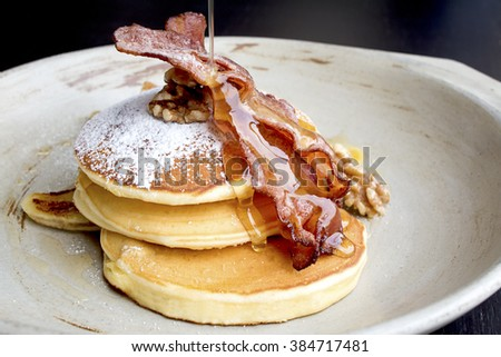 Stack of delicious pancakes with bacon, honey, nuts and caramelize banana - stock photo