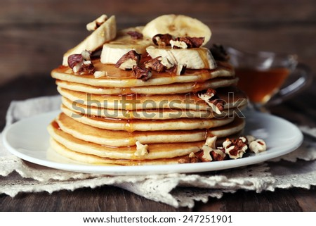 Stack of delicious pancakes with chocolate, honey, nuts and slices of banana on plate and napkin on wooden background - stock photo