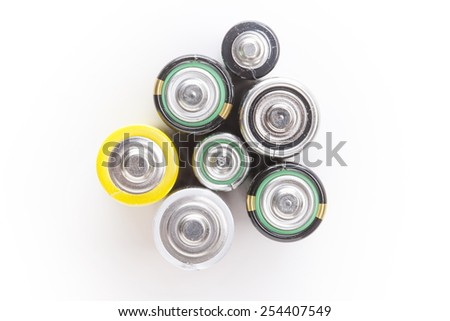 Stack of different batteries on white background. Image with shallow depth of field. - stock photo