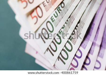stack of different euro bank notes on green background - stock photo