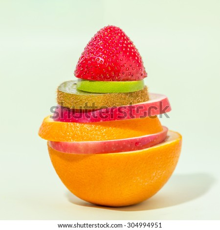 stack of different fruit slices on sofe green background, concept for health care, fruit punch - stock photo