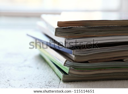 Stack of different magazines on the wooden table - stock photo
