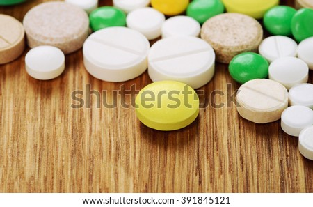 Stack of different pills isolated on wooden background - stock photo