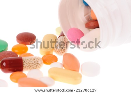 Stack of different pills  near the opened container on white background - stock photo