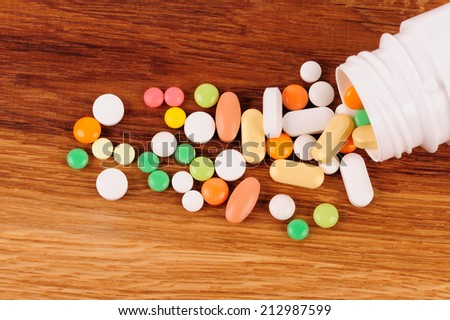 Stack of different pills  near the opened container on wooden desk - stock photo