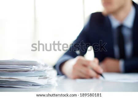 Stack of documents at workplace and male employee on background - stock photo