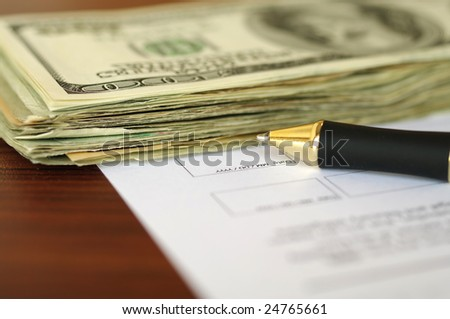 Stack of dollars and pen on a document page. See more like it in my portfolio.