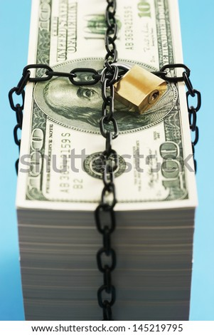 Stack of Dollars secured by padlock and chain - stock photo