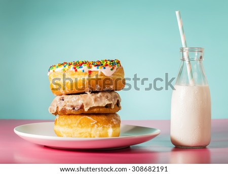 Stack of donuts with milk in a jar on pastel pink and blue background - stock photo