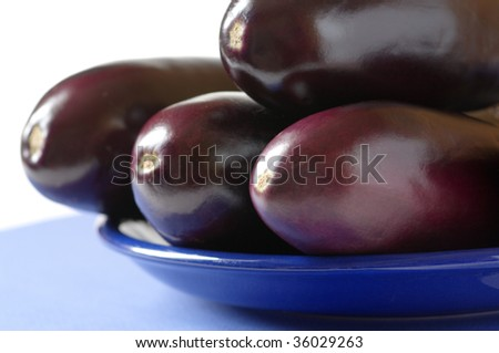 Stack of eggplants close-up in blue plate.