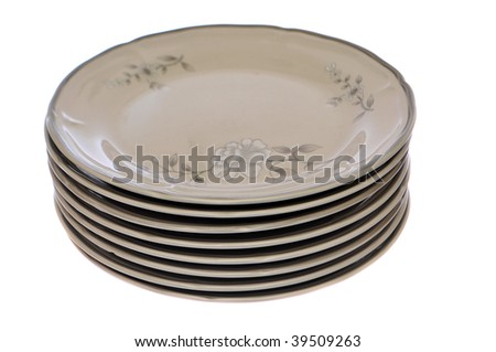 Stack of eight white plates with a flower design on them isolated on white background