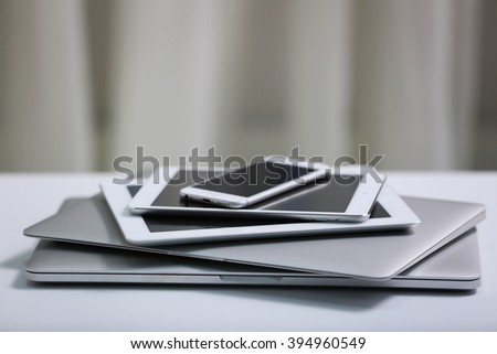 Stack of electronic devices on a white desk - stock photo