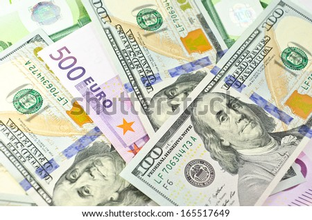 Stack of euro and new dollar banknotes in soft focus - stock photo