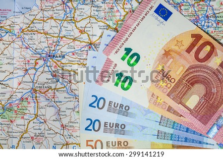 Stack of Euro Travel Money and map of Europe over Paris, France - stock photo